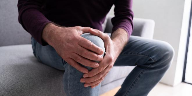 a man holding his knee for support